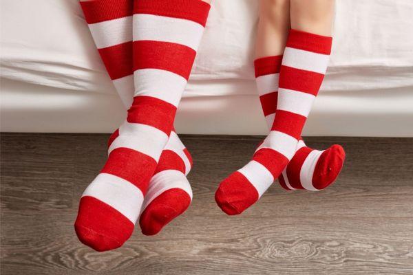 Egy ágyon két gyerek ül, lábukon lábgombásodást eltakaró piros-fehér csíkos zokni.