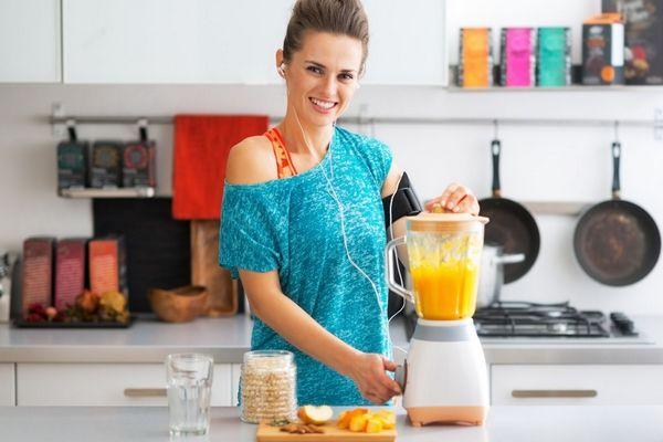 Egy konyhában egy fiatal nő turmixot készít gyömbérből, almából, borsmentából, korianderből és ananászból.