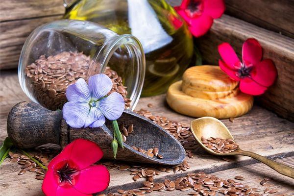A szív- és érrendszeri betegségeket visszafordító lenmagolaj egy üvegben, mellette lenmagok, és lenvirágok.