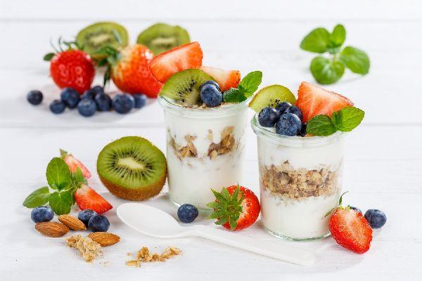 Egy asztalon két üvegpohárban joghurt, rajtuk és mellettük gyümölcsök és magvak elszórva, eper, fekete áfonya, kivi, mandula.