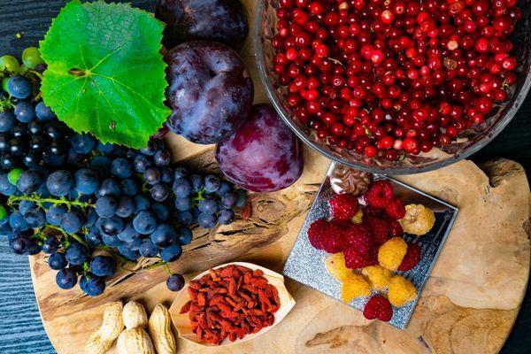 Egy asztalon gyulladáscsökkentő öregedésgátló resveratrolt tartalmazó gyümölcsök és magvak, kék szőlő, áfonya, szilva málna sárga málna, goji bogyó, földi mogyoró.