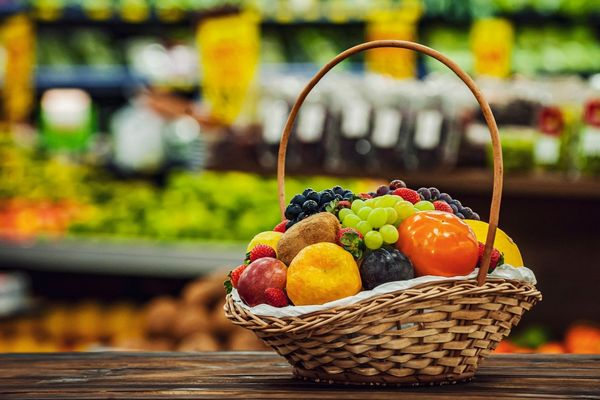 Rostban gazdag gyümölcsök egy kosárban, narancs, szilva, szőlő, eper, alma, barack és paradicsom.