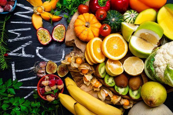 Egy asztalon C-vitamin felirat, mellette sok C-vitamint tartalmazó gyümölcs és zöldség, banán, dinnye, paradicsom, füge, fokhagyma, karfiol, málna, narancs, kivi, körte.