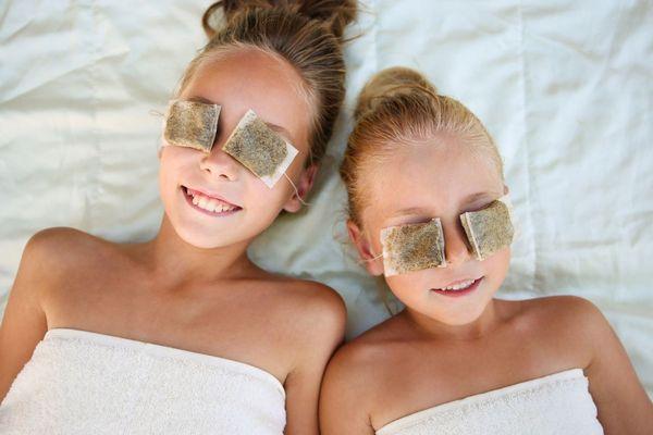 Egy ágyon két kislány fekszik, szemeiken használt teafilterek.