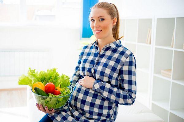 Egy kék kockás kismama ül, mezében egy üvegtál, tele zöldséggel, salátával, uborkával, paradicsommal, paprikával.