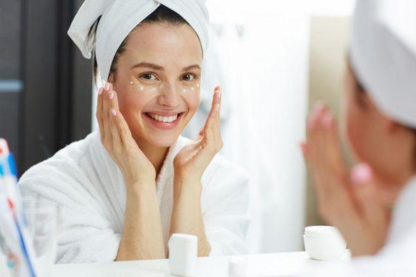 Egy fiatal nő a fürdőszobában fehér törölközővel a fején a két kezével arcát krémmel bekeni.