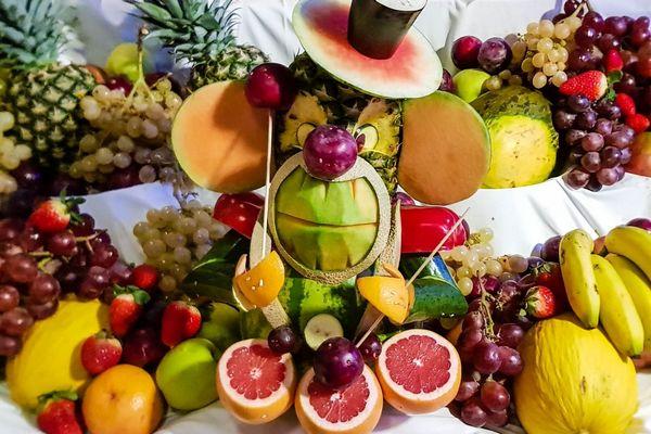 Egy asztalon sok gyümölcs és zöldség, eper, szőlő, banán sárga dinnye, narancs, ananász, szilva, dinnye.