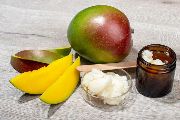 Egy asztalon egész és szeletelt mangó, mellette egy üvegben mangóvaj.