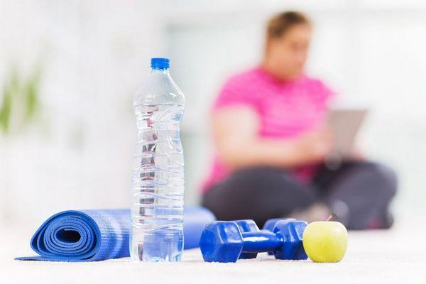 Műanyag vizespalack, mellette fitneszmatrac, súlyzó és alma, mögötte egy túlsúlyos nő ül.