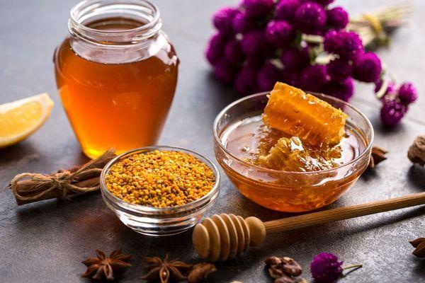 Egy asztalon üvegben méz, mellette propolisz egy tálban és méhpempő, csillagánizs, dió, citrom, virágok.