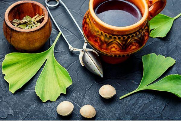 Egy szürke asztalon kerámia tálban és mellette Gingko biloba és bögrében Gingko bilobából készült tea.