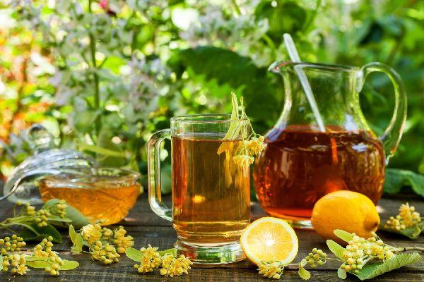 Egy asztalon üveg kancsóban és üveg pohárban hárstea, mellettük hársvirágok és citrom.
