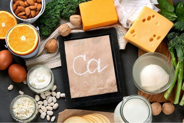Egy asztalon kalciumot tartalmazó élelmiszerek, sajtok, tej, túró, bab, dió, tojások, brokkoli, mandula, narancs, fodros kel.