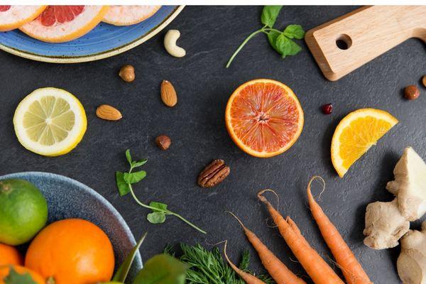 Egy szürke asztalon kollagéntermelést fokozó táplálékok, sárgarépa, narancs, citrom, magvak.