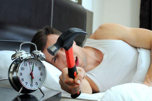Egy fiatal férfi az ágyban fekszik, kezében egy kalapács, amellyel az ébresztőórát akar megütni.