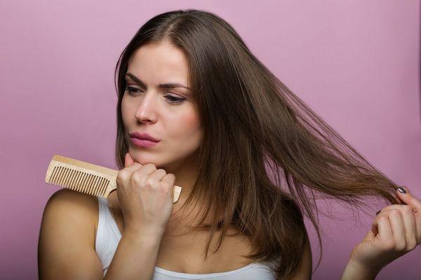 Egy lila háttér előtt fiatal lány aggódó arccal egy fésűt tart a kezében, miközben a haját fogja.