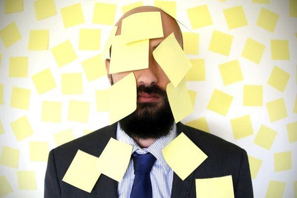 Egy stresszes, öltönyös, szakállas férfi tele van aggatva sárga papírokkal.