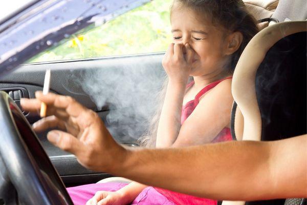 Egy autóban apa és lánya autóban ül, az apa dohányzik vezetés közben, a kislányt zavarja a füst és befogja az orrát.