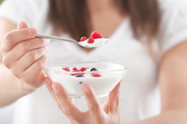 A bélflóra egyensúlyát támogató joghurtot eszik egy lány, a gyümölcsös joghurtos tálat tartja a kezében.