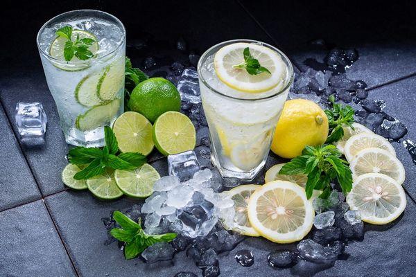 Egy szürke asztalon üveg poharakban citromos víz, mellettük citrom, citromszeletek és lime, illetve jégkockák.