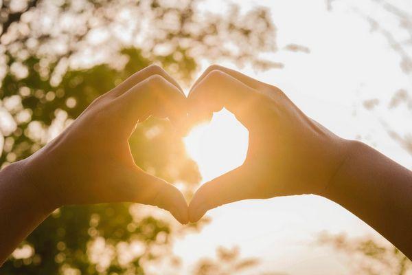 Szívet formál két kezével egy férfi tűző napsütésben.