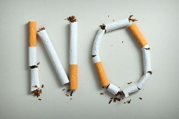 Egy asztalon no felirat cigarettákból kirakva.