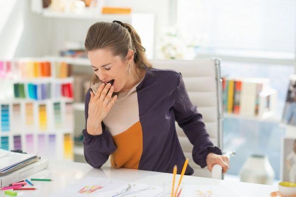 Egy fiatal nő az irodában az íróasztalnál ül, miközben ásít.