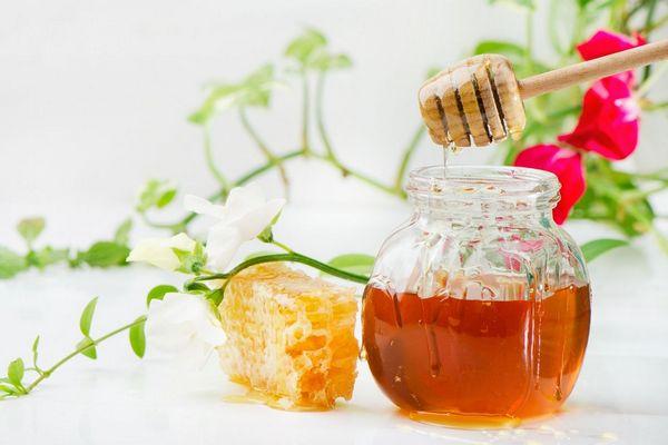 Egy asztalon egy üvegben méz, amelyből egy csurgatóval mézet csurgatnak, mellette egy lépesméz.