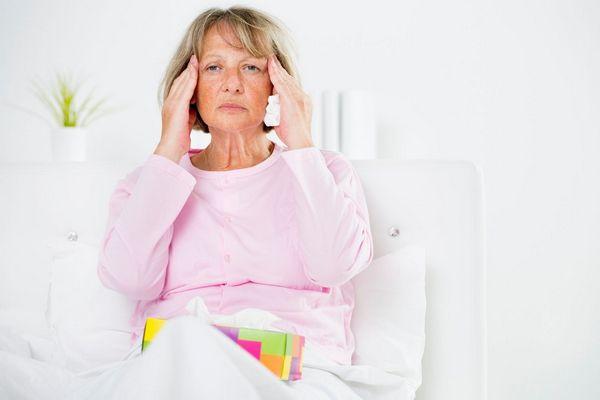 Egy idős hölgy rózsaszínű blúzban a két kezével a migrénes fejét fogja.