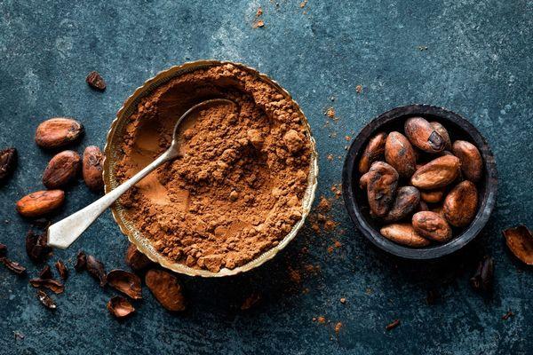 Egy szürke asztalon egy tálban kakaópor, mellette kakaóbabszemek.