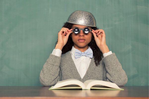 Egy zöld háttér előtt egy egyetemista lány vastag szemüveget visel, fején agyat mintázó fém sisak.