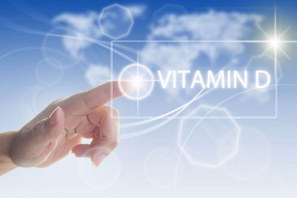 Egy férfi ujjával egy Vitamin D feliratra mutat, a háttérben sugárzó Nap és felhők.