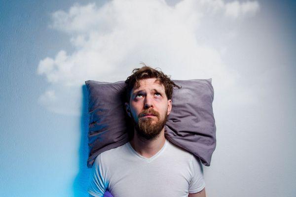 Egy szakállas férfi ágyban fekszik karikás szemmel, mögötte felhős ég, álmatlanságban szenved.