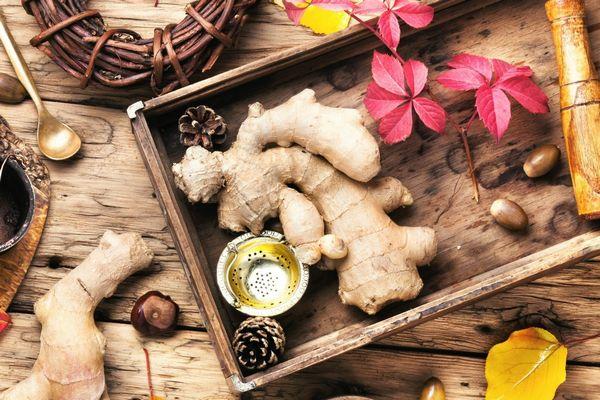 Egy asztalon dobozban és mellette gyömbér, színes őszi levelek, gesztenye és toboz.