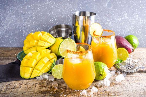 Egy asztalon felvágott mangó, mellette üveg pohárban mangólé és lime.