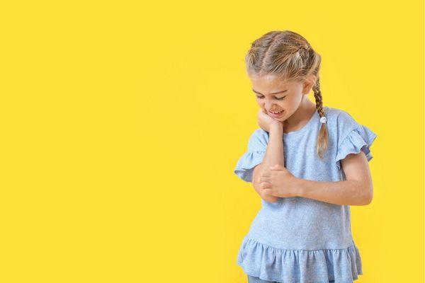 Egy sárga háttér előtt egy kék ruhás kislány áll, kezével vakarja az ekcémás karját.