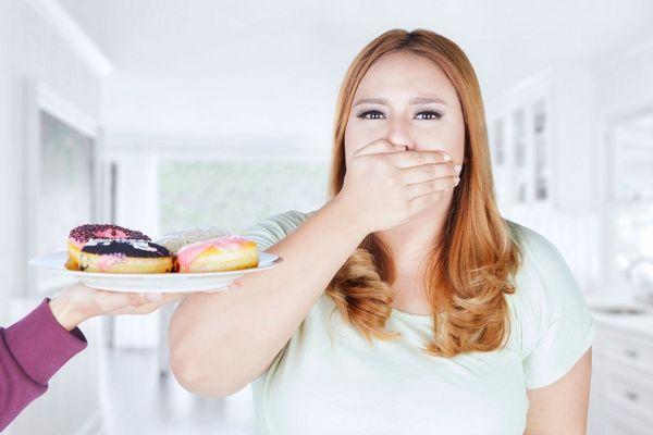 Egy túlsúlyos, elhízott nő a kezével a száját befogja, mert egy kéz tányéron donat fánkokat kínál neki.