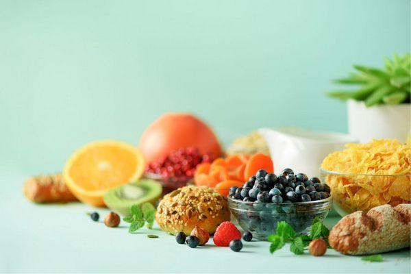 Egy asztalon sok vegán élelmiszer, fekete áfonya, málna, mogyoró, citrom, kivi, sárgabarack, menta, teljes kiőrlésű kenyér és zsemle.