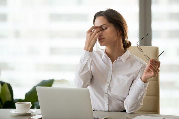 Egy irodában fiatal nő a szemeit becsukja, szemüvegét a kezében tartja, mert a feje megfájdult a monitor nézésétől.