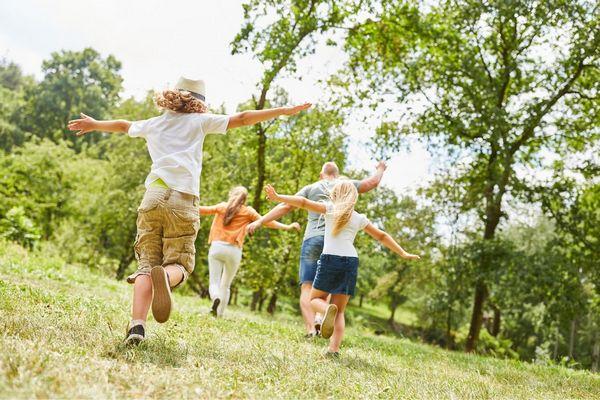 Egy erdőben egy család boldogan szalad, kezeiket repülőtartásban tartják.