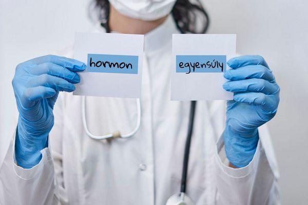Egy fehér köpenyes orvos kék gumikesztyűben két papírt tart, amelyre hormonegyensúly található.