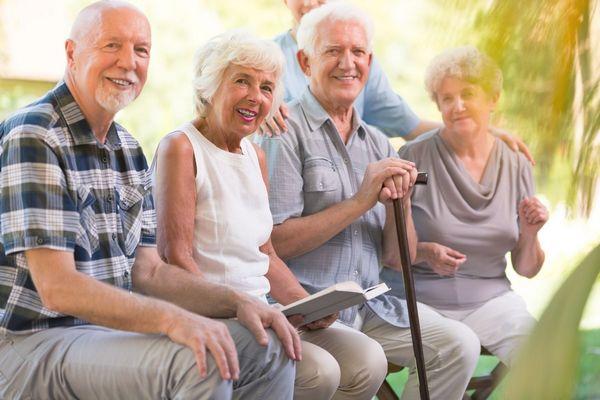 Napsütéses délelőtt öt idős nyugdíjas ember ül a napon és mosolyog.