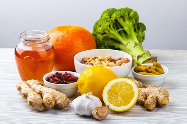 Egy asztalon üvegben méz, narancs, brokkoli, citrom, gyömbér, fokhagyma és magvak kis tálakban.