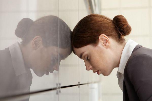 Egy fiatal nő az irodában fáradtan, kimerülten előre dől a szekrényre és alszik.