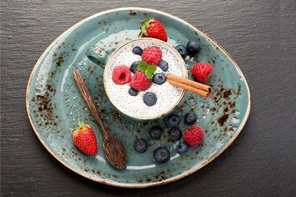 Egy szürke asztalon világos szürke tányéron eprek, fekete áfonyák, fakanalak, mellettük bögrében chiamagból készült puddig gyümölcsökkel.