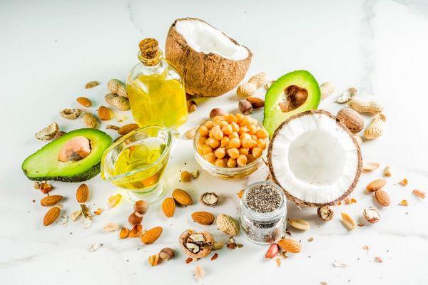 Egy asztalon magas zsírtartalmú növények, kókusz, avokádó, mandula, dió, mogyoró, és üvegekben olajok.