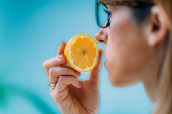 Egy szemüveges nő szaglásvesztésben szenved, narancsot próbál szagolni.
