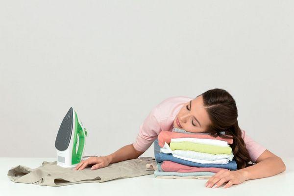 Egy fiatal nő alszik, a fejét kivasalt ruhákra hajtja, mellette ruha és vasaló.