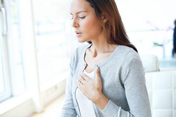 Asztmától és más légzőszervi problémáktól szenvedő fiatal nő kezét a mellkasára helyezik, nehezen veszi a levegőt.