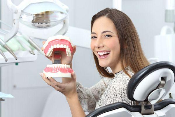 Egy fogorvosi rendelőben egy nevető lány ül a fogorvosi székben, kezében egy műanyag fogsort tart.